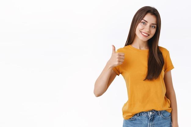 Vriendelijke, goed uitziende glimlachende, gelukkige jonge vrouw beoordeel goed product, geef positieve feedback, antwoord met goedkeuring, duim omhoog en grijnzend, beveel perfecte service aan, witte achtergrond