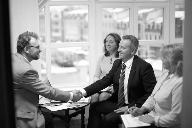 Vriendelijke handdruk van zakenpartners op kantoor. het concept van partnerschap