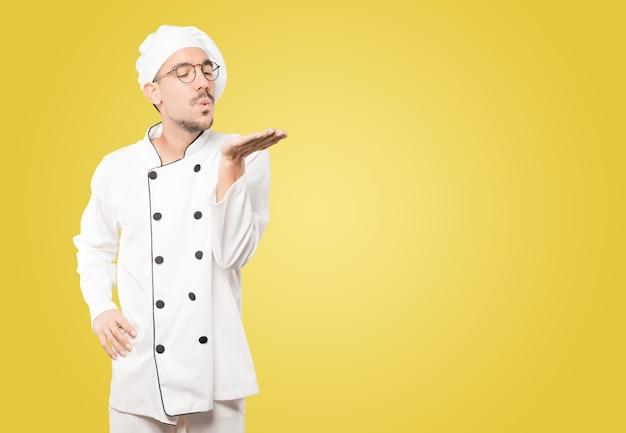 Vriendelijke jonge chef-kok die een gebaar maakt van het verzenden van een kus met zijn hand
