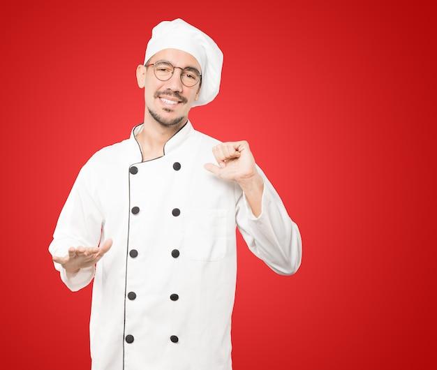 Vriendelijke jonge chef-kok doet een gebaar van kalmte bewaren