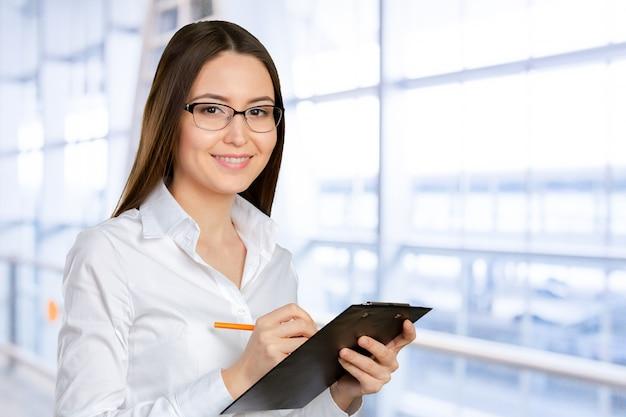 Vriendelijke jonge glimlachende zakenvrouw met klembord en pen