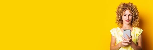 Vriendelijke jonge krullende vrouw kijkt naar de telefoon op een gele achtergrond. banner