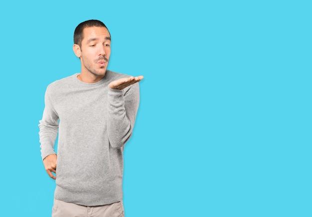 Vriendelijke jonge man die een gebaar maakt van het verzenden van een kus met zijn hand