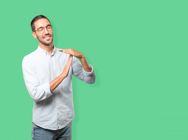Vriendelijke jonge man die een time-out gebaar maakt met zijn handen