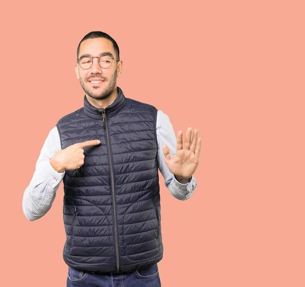 Vriendelijke jonge man doet een gebaar van blijf kalm