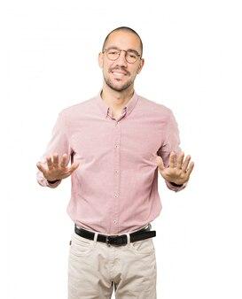 Vriendelijke jonge man doet een gebaar van kalmte bewaren