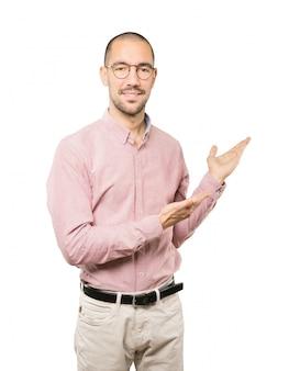 Vriendelijke jonge man een gebaar van welkom maken