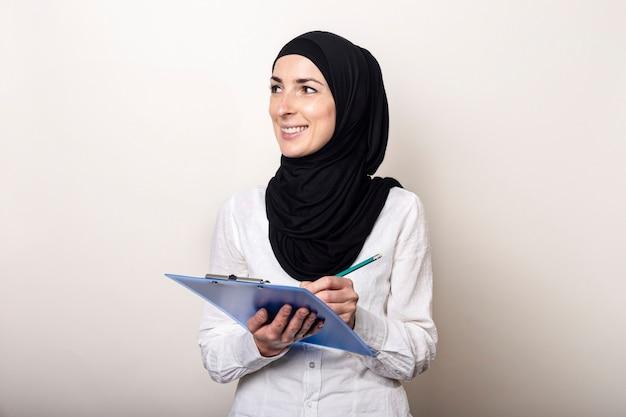 Vriendelijke jonge moslimvrouw in een wit overhemd en hijab houdt een klembord met een glimlach vast