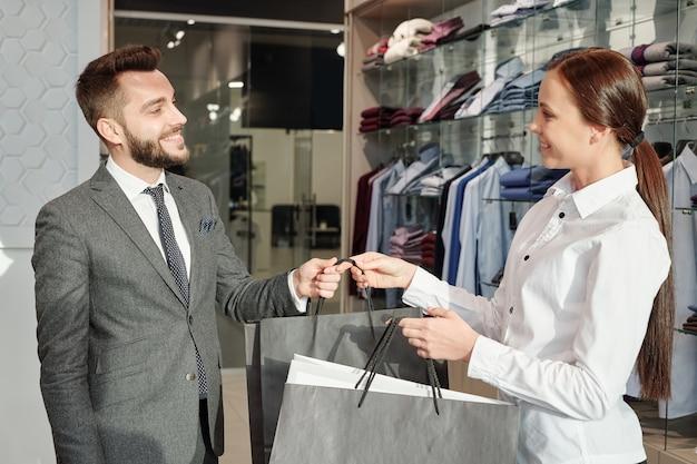 Vriendelijke jonge verkoper van kledingwinkel boodschappentassen geven aan tevreden mannelijke klant