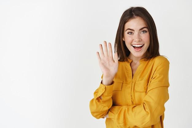 Vriendelijke jonge vrouw die met de hand zwaait en hallo zegt, je begroet met een vreugdevolle glimlach, staande over een witte muur