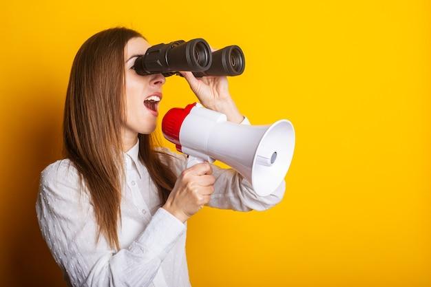 Vriendelijke jonge vrouw houdt een megafoon in haar handen en kijkt door een verrekijker op een gele achtergrond. inhuurconcept, hulp gezocht. banier.