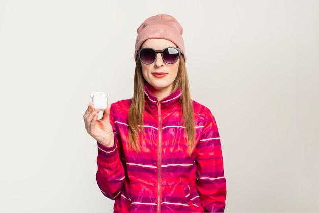 Vriendelijke jonge vrouw in glazen, hoed en roze sportjasje met een smiley houdt draadloze koptelefoon