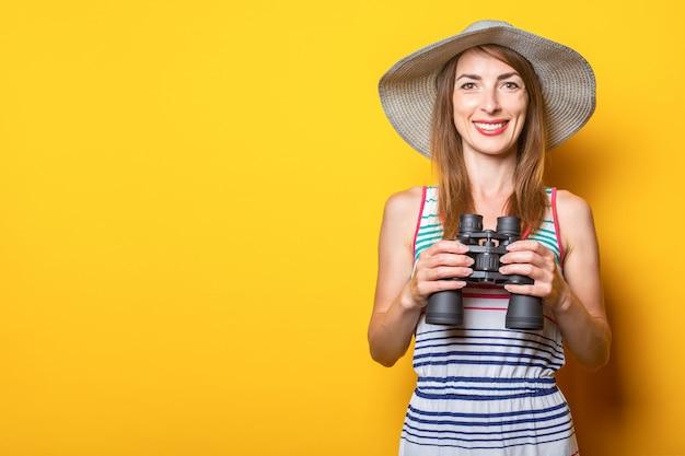 Vriendelijke jonge vrouw lachend met een hoed en een gestreepte jurk met verrekijker op een gele ruimte.
