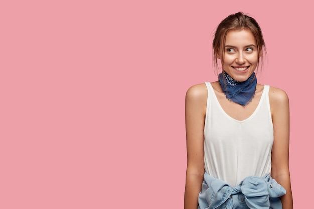 Vriendelijke jonge vrouw met bril poseren tegen de roze muur