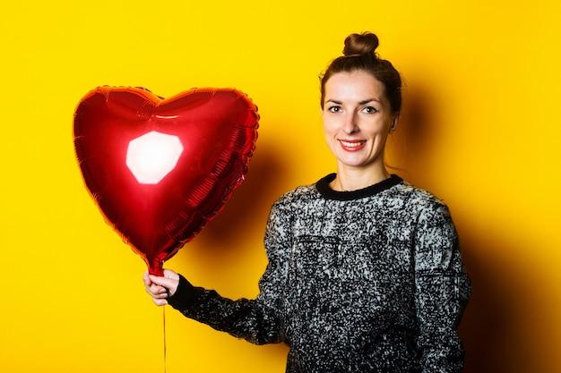 Vriendelijke jonge vrouw met een rode luchtballon in de vorm van een hart op een gele achtergrond.