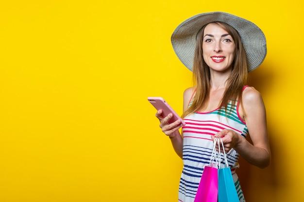 Vriendelijke jonge vrouw met een telefoon met boodschappentassen