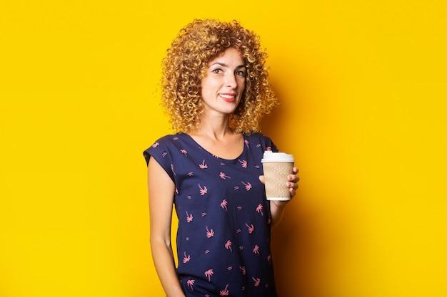 Vriendelijke jonge vrouw met krullend haar houdt een papieren beker op een gele ondergrond