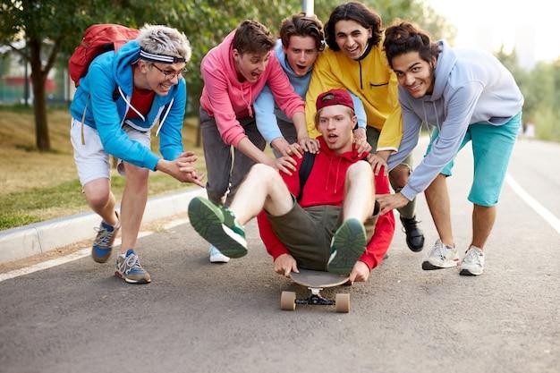 Vriendelijke jongens rijden hun kerel op skateboard