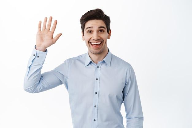 Vriendelijke kantoormedewerker die met de hand zwaait en hallo zegt, glimlacht, hallo zegt, groet, warm welkom heet en er vrolijk uitziet, tegen een witte muur staat