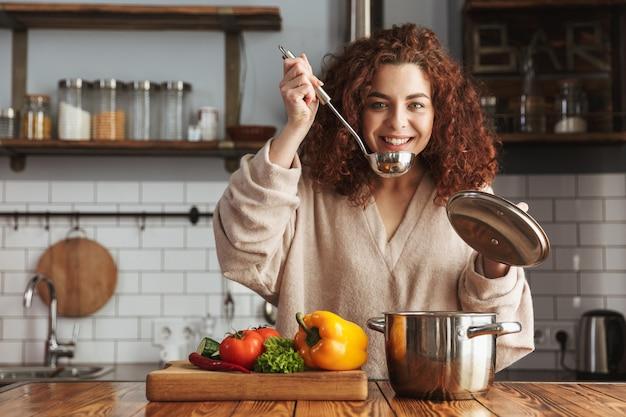 Vriendelijke kaukasische vrouw die kooklepel vasthoudt terwijl ze soep met verse groenten eet in de keuken thuis