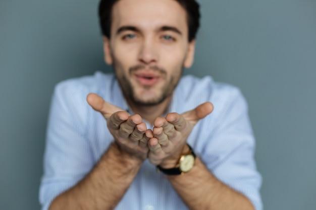 Vriendelijke kusjes. selectieve focus van mannelijke handen die bij elkaar worden gehouden terwijl je luchtkussen verzendt