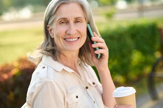 Vriendelijke lachende vrouw communiceren via smartphone