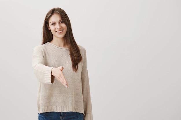 Vriendelijke lachende vrouw groet persoon met handdruk
