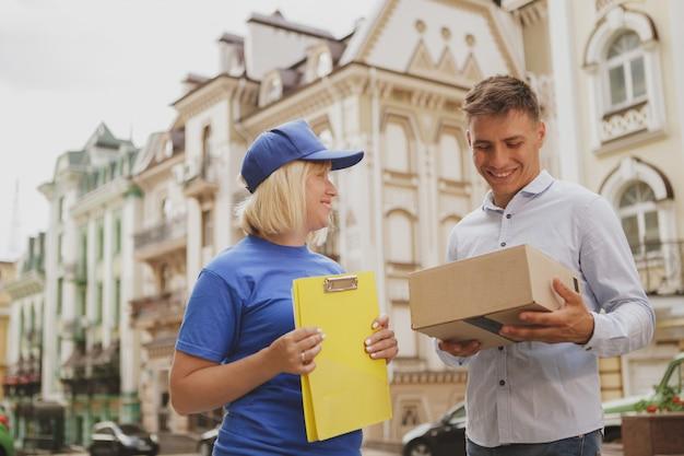 Vriendelijke leveringsvrouw in blauw uniform op de stadsstraat
