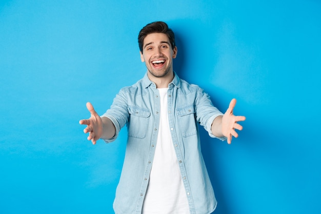 Vriendelijke man die zijn handen naar voren uitstrekt en je verwelkomt, gasten begroet of knuffelt, staande tegen een blauwe achtergrond