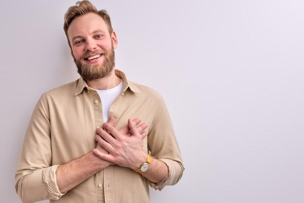 Vriendelijke man groet, dankbaarheid uiten hand in hand op de borst, glimlachend in de camera geïsoleerd op een witte achtergrond