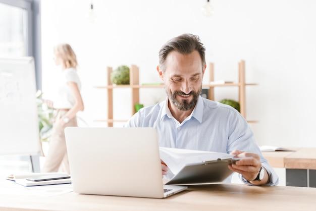 Vriendelijke man manager die op laptopcomputer werkt