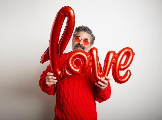 Vriendelijke man met bril met een rode ballon met het woord liefde op witte achtergrond.