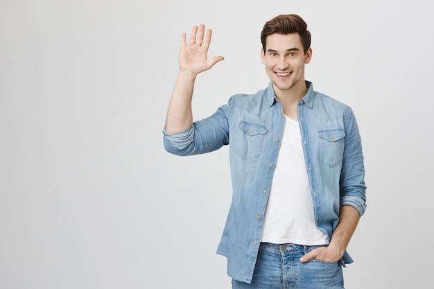 Vriendelijke man zwaait met de hand en zegt hallo