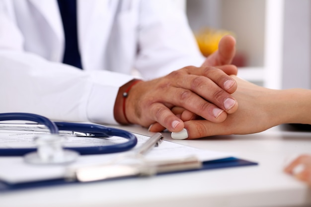 Vriendelijke mannelijke arts houden vrouwelijke arm in kantoor