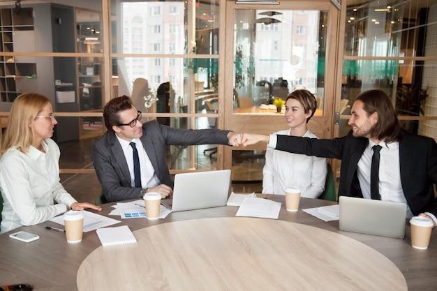 Vriendelijke mannelijke collega's of partners vuist stoten op teamvergadering