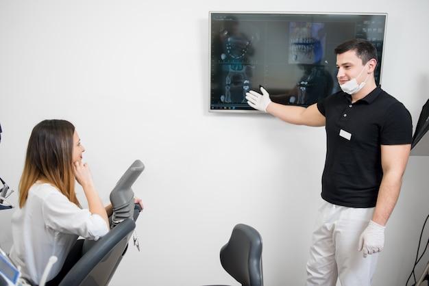 Vriendelijke mannelijke tandarts die aan vrouwelijke patiënt haar tand x-ray beeld op computermonitor toont