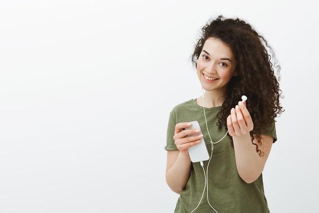 Vriendelijke meid wil muziek met ons delen. portret van onbezorgde, vrolijke vrouw met krullend haar, breed glimlachend en smartphone vasthoudend, oortelefoon naar toe trekken