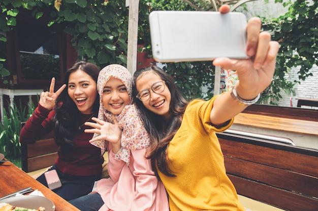 Vriendelijke meisjes maken selfie in café