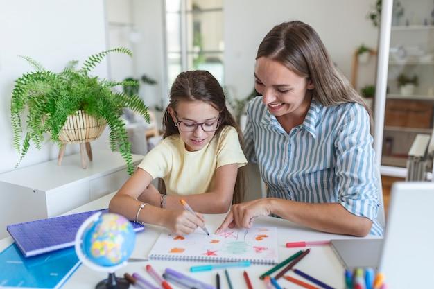 Vriendelijke moeder die haar dochter helpt bij het maken van huiswerk. moeder helpt dochter met huiswerk tijdens covid-19 coronavirus en leert thuis. glimlachende moeder die meisje helpt met huiswerk