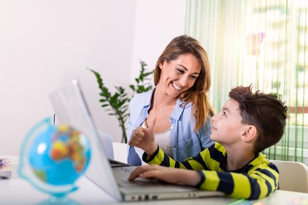 Vriendelijke moeder die haar zoon helpt die huiswerk online doet. e.