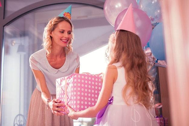 Vriendelijke moeder. vrolijke jonge vrouw die en naar haar dochter glimlacht leunt terwijl het haar een groot verjaardagsgeschenk geeft