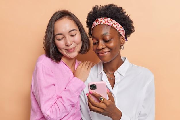 Vriendelijke multi-etnische beste vriendinnen kijken graag naar interessante video via smartphone die is verbonden met draadloos internet, hebben vrije tijd en gebruiken moderne technologieën geïsoleerd op beige
