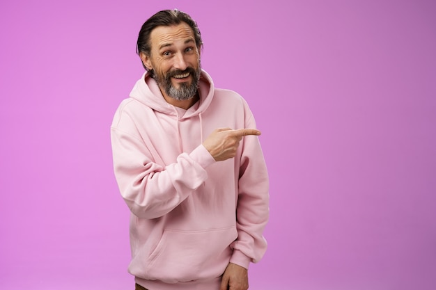 Vriendelijke onbezorgde blanke bebaarde man in roze hoodie naar rechts wijzend familieleden glimlachend trots opgetogen tonen lege kopie ruimte reclame, poseren paarse achtergrond.