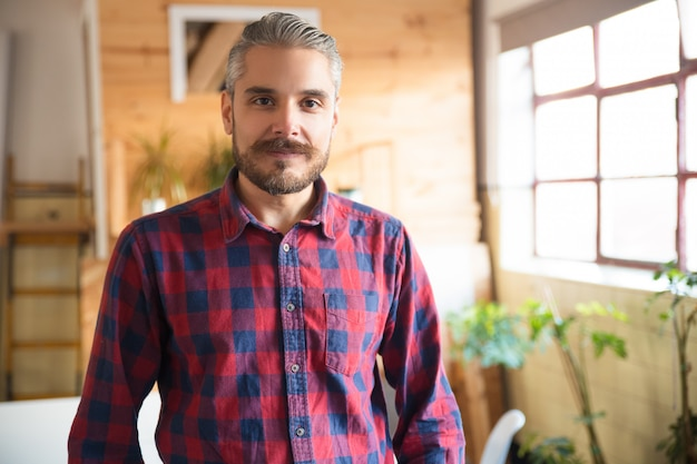 Vriendelijke ondernemer poseren in moderne kantoor