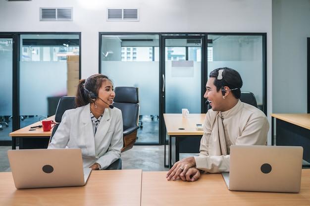 Vriendelijke operator aziatische collega-agent met hoofdtelefoon en laptop praten roddels tussen werken in callcenter