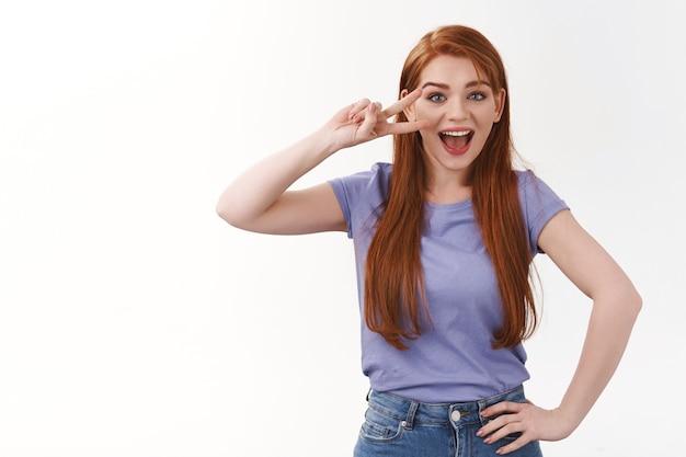 Vriendelijke, optimistische mooie roodharige vrouw, lang gemberkapsel, paars t-shirt dragen, promo uitnodigen, vredes- of overwinningsteken boven oog tonen, geamuseerd open mond, glimlachen, witte muur