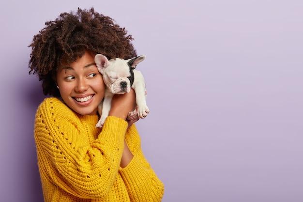 Vriendelijke optimistische vrouw koude rillingen met kleine puppy