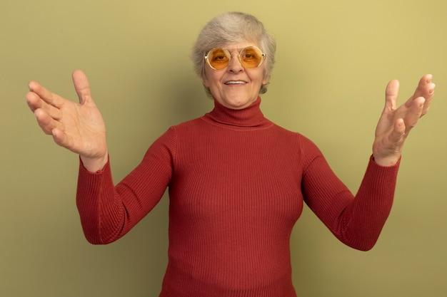 Vriendelijke oude vrouw met een rode coltrui en een zonnebril die gasten ontmoet met wijd open armen, ik ben blij je gebaar te zien geïsoleerd op een olijfgroene muur