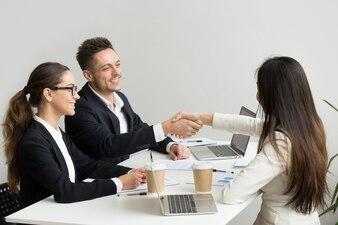 Vriendelijke partners handshaking op groepsbijeenkomst bedankt voor succesvol teamwork