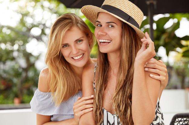 Vriendelijke positieve vrouwen omhelzen elkaar, steunen elkaar terwijl ze uitrusten op het terras, uiten homoseksuele relaties. vrouwen lesbiennes knuffelen als date samen. mensen, vriendschap en relatie